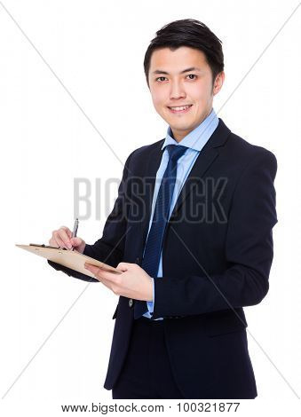 Asian young businessman write on the clipboard