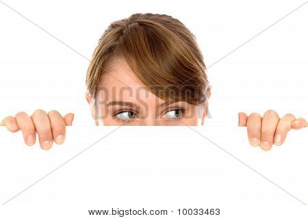 Woman peeping over a blank billboard