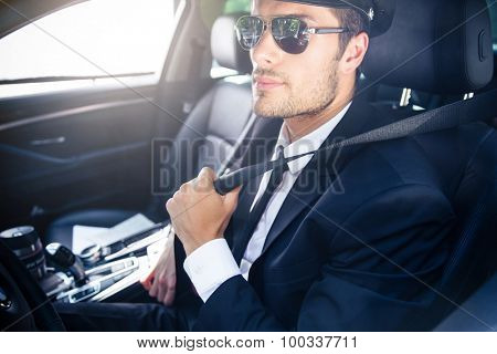 Portrait of a handsome male chauffeur in sunglasses sitting in a car