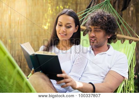 Portrait of a smiling couple reading book together outdoors on hammok