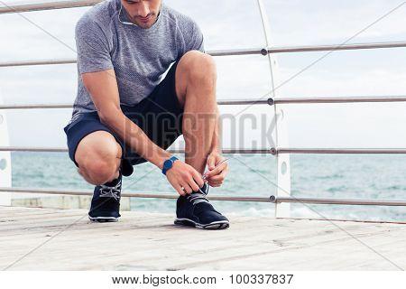 Portrait of a sports man tie shoelaces outdoors