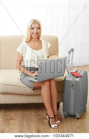 Woman with suitcase and laptop sitting on sofa indoors
