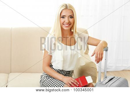 Woman with suitcase sitting on sofa indoors