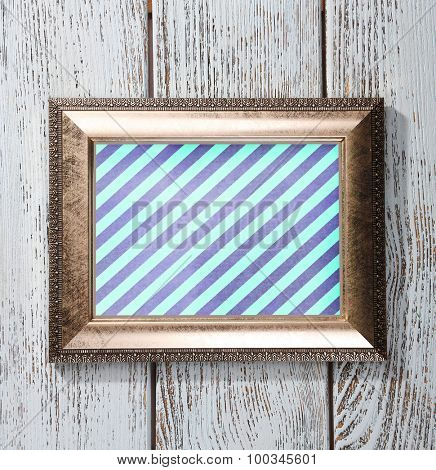 Old frame with striped canvas on wooden background