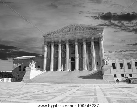 Supreme court building exterior with sunset sky in black and white.