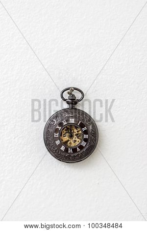 Old Pocket Watch Hanging On The White Wall