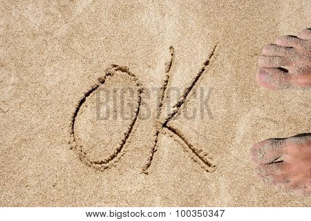 Concept or conceptual ok text handwritten in sand on a beach background with feet