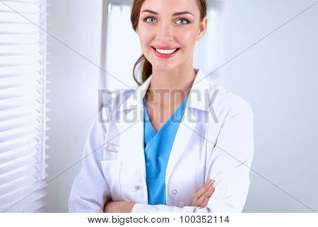 Woman doctor is standing near window