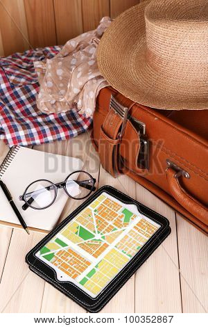 Tablet with map gps navigation application and travel accessories, close-up