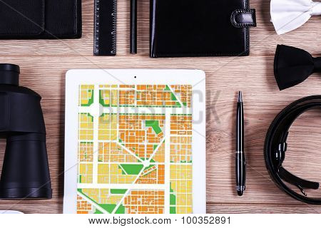 Tablet with map gps navigation application and male accessories, close-up