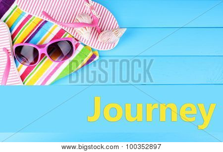 Journey concept. Beach accessories on blue wooden background