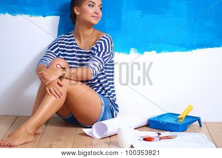 Portrait of female painter sitting on floor after painting