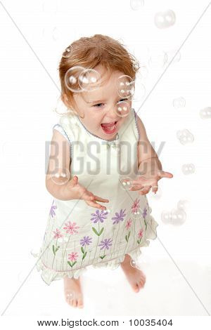 Laughing 2 Year Old Girl Catching Bubbles