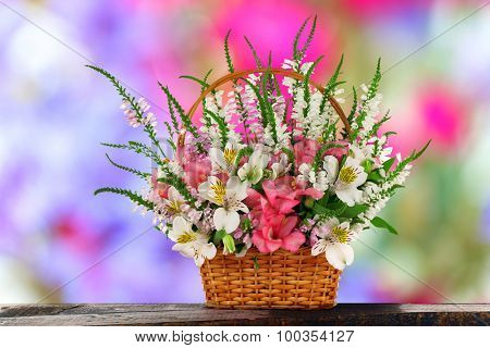 Beautiful wildflowers in wicker basket on abstract background
