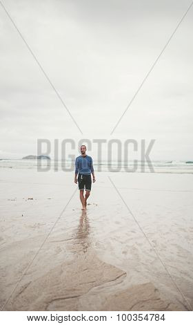 Man Walking On The Sand Of The Beach