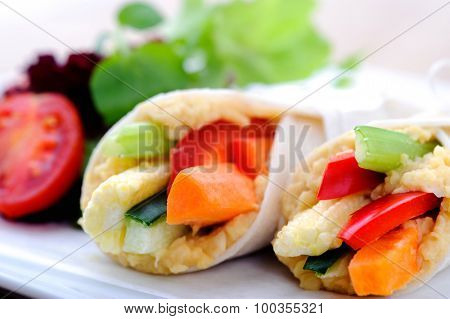 Mini tortilla wraps with raw vegetable sticks, shallow depth of field