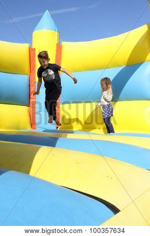 Two Children playing on a bouncy castle