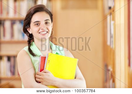 Close-up of a cute female student standing with notebooks at the library