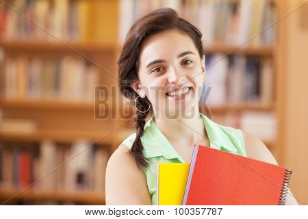 Beautiful female student standing with notebooks at the library