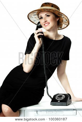 Portrait Of A Beautiful Brown-eyed Woman In A Hat With A Vintage Telephone