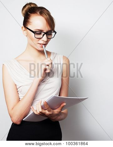 Business, finance and people concept:  young  business woman hold pages of paper. Paperworker. Over grey background.