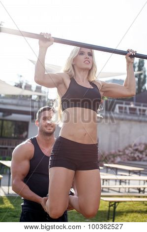 Fitness Trainer Helps Woman Pull Up