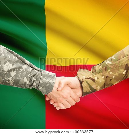 Men In Uniform Shaking Hands With Flag On Background - Benin