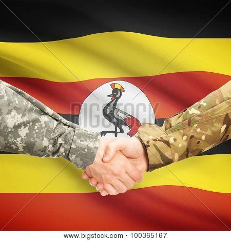Men In Uniform Shaking Hands With Flag On Background - Uganda