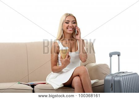 Woman with suitcase sitting on sofa isolated on white