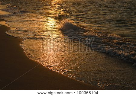 Wave Sliding Down Back To The Sea From Golden Sand Beach In Stunning Sunset Light