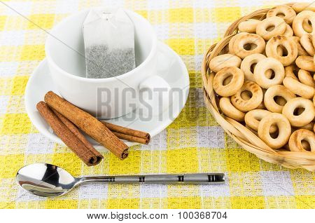 Packet Of Tea In Cup, Cinnamon And Small Bread Rings