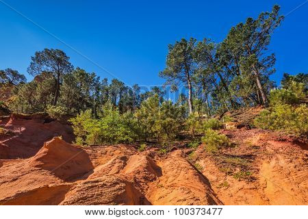 Roussillon, Red village of Provence. Picturesque canyon of production of ochre - natural paint. Multi-colored outcrops - from yellow to red-orange. Green trees create beautiful contrast from ochre