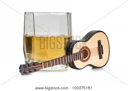 Glass of whiskey and guitar on a white background