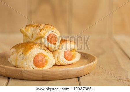 Danish Pastry With Sausage On Wooden Dish