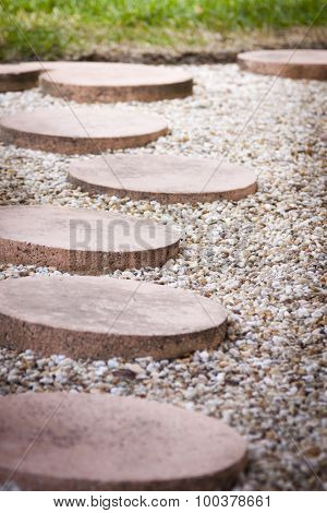 A path of circular stepping stones in a home garden, shallow depth of field.