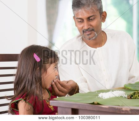 Indian family dining at home. Candid photo of India people eating rice with hands. Parent feeding child.