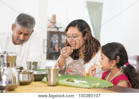 Indian family dining at home. Candid photo of India people eating rice with hands. Asian culture.