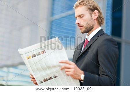 Handsome businessman reading a newspaper