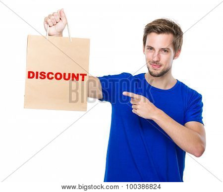 Man finger point to the shopping bag and showing a word discount
