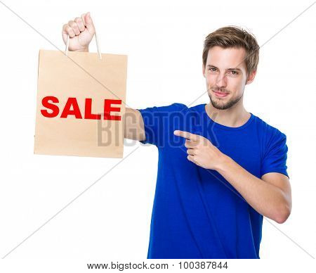 Man finger point to the shopping bag and showing a word sale