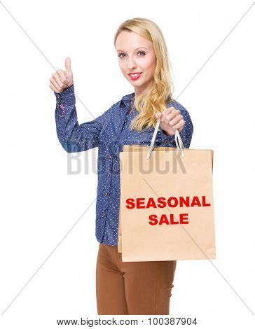 Woman with shopping bag and thumb up for showing phrase of seasonal sale