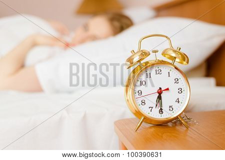 Retro alarm clock with sleeping lady on background