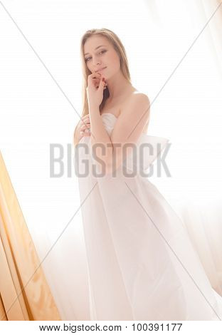 Young happy smiling lady in white long cloth by window