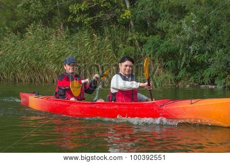 The couple goes kayaking on the river.