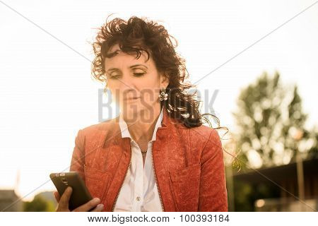 Senior woman looking to phone at sunset