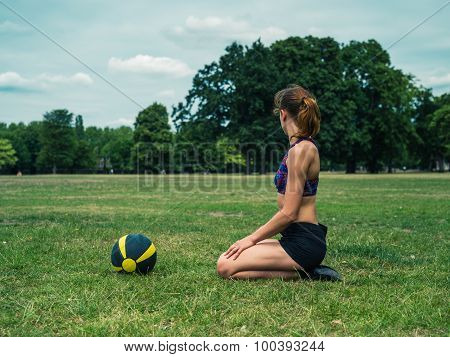 Woman Sitting On Grass With Medicine Ball