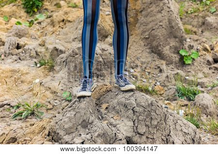 Legs Of Woman Standing On Mound Of Dirt