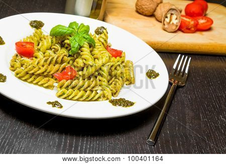 Dish Of Pasta With Pesto Genovese Sauce And Vegetables, Tomato And Basil On Black Wood Table Near Fo