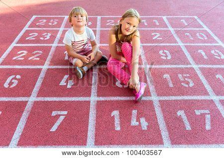 Two cute kids resting on school yard
