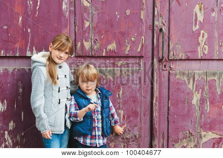 Portrait of two adorable kids outdoors, wearing warm coats